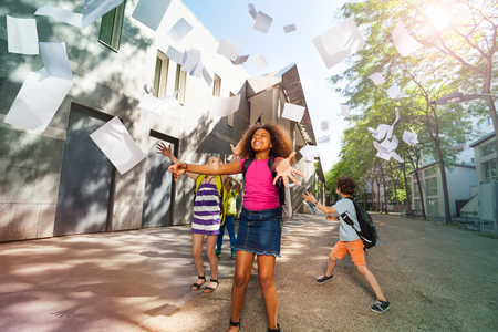 hooray: Girl throws papers happy and standing near school Stock Photo