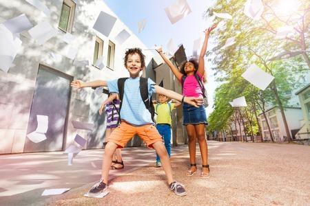 Gelukkige jongen gooit papieren in de lucht erg opgewonden