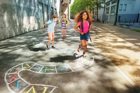 Three happy school age kids play hopscotch Stock Photo