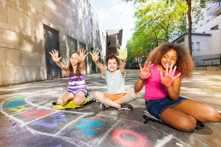 Kids show palms colored in chalk drawing game