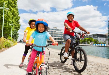 African children cycling along a river embankment