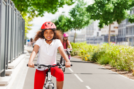 Happy African girl riding bicycle on cycle path