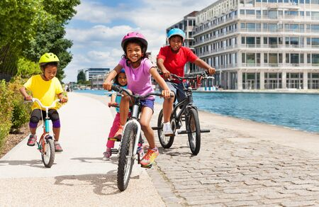 Cute African girl riding bicycle with her friends Stock Photo