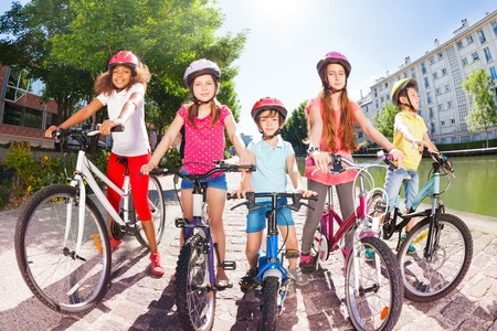 Children with bicycles on embankment of the river