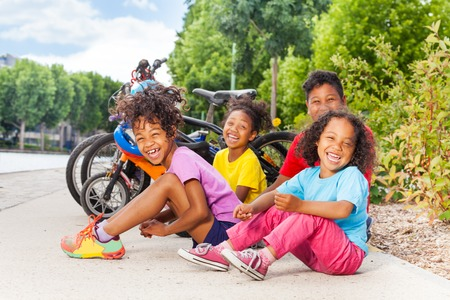 Laughing African kids sitting on the bike path