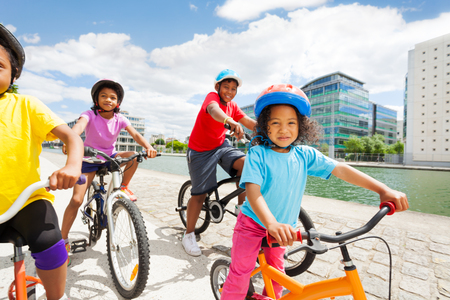 African girl in safety helmet cycling with friends
