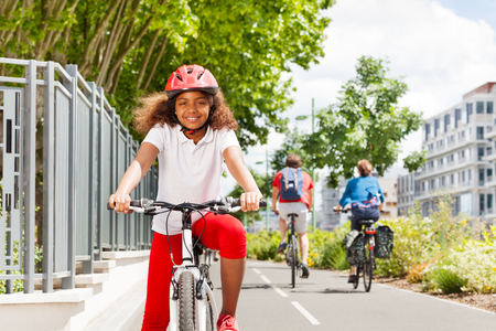 Happy African girl cycling on bicycle path in city