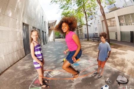 Meisjes en jongens spelen elastisch touwspel samen Stockfoto