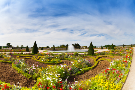 Panoramic view of famous garden parterres with blossoming flowers and fountains in summer, Versailles, France
