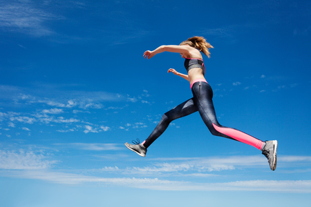 Low angle view portrait of female athlete remaining stationary in air while jumping or running against blue sky background Фото со стока