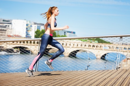 Side view portrait of sporty young woman running across the city streets Фото со стока