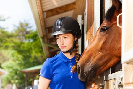 ジョッキーの頭蓋骨、馬で安定して立っている身に着けている美しい若い女性の肖像画
