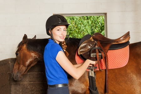 Portrait of beautiful young woman in jockey uniform, standing inside the riding stable and fitting a saddle while preparing her bay horse