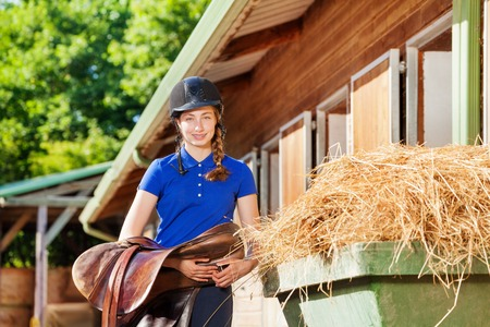 Portrait of beautiful young woman in jockey wear, holding saddle standing outside riding stable Banco de Imagens