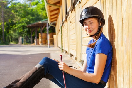 Close-up portrait of beautiful jockey girl sitting on the floor at riding stable and looking at camera Stock Photo