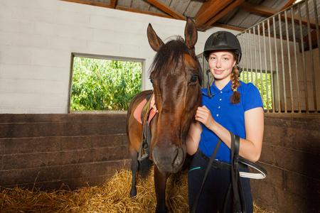 美しい女性騎手、安定の中に立っていると彼女の馬を抱き締める