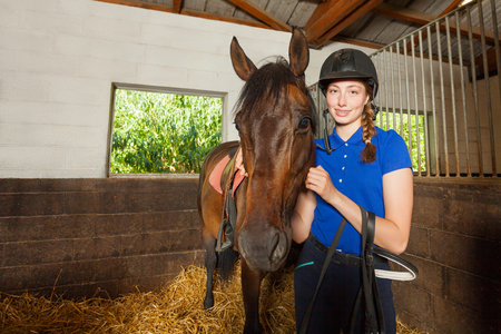 Beautiful female jockey standing inside the stable and hugging her bay horse