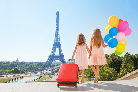 Two little travelers, age diverse girls with suitcase and balloons bouquet, holding hands while walking around Paris in summer