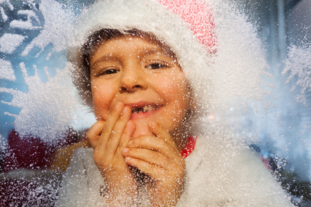 Boy portrait with New Year hat behind cold window