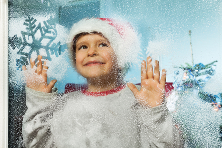 Boy in Christmas hat behind window with snoflakes