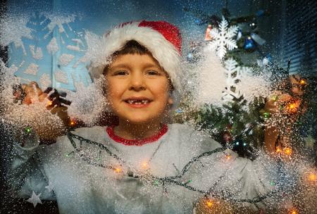 Boy in Santa hat and Christmas tree behind window Stock Photo