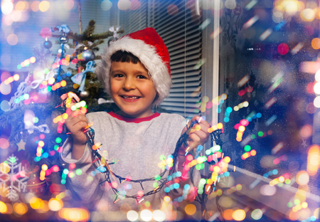 Boy with New Year lights before Christmas Stock Photo
