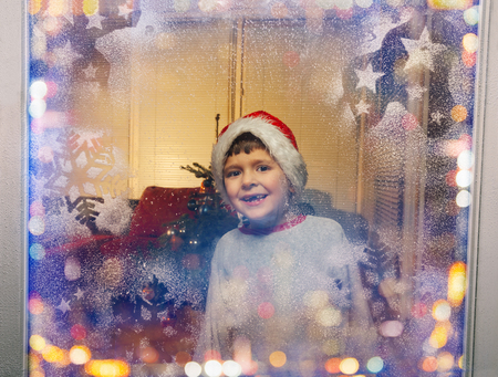 Little boy looking though frosty snowflakes window Stock Photo