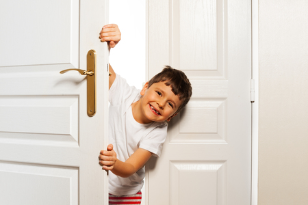 Little boy looks behind room door with smile