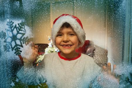 Boy in Santa hat behind frozen window with snow
