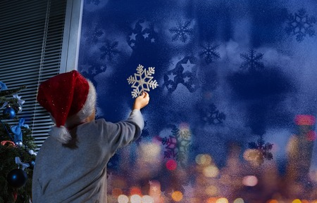 Little boy putting snowflake on the window Stock Photo