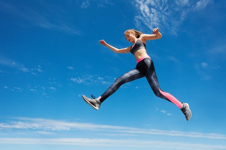 Female athlete remains in air while running Banco de Imagens