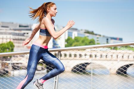 Sportvrouw die in de stadsstraten sprint
