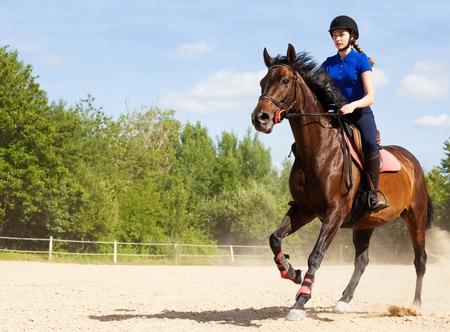 Female jockey galloping on horseback at racetrack
