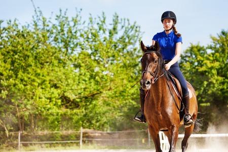 美しい女性騎手が馬にまたがって座っています。