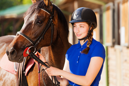 Beautiful jockey girl with her purebred bay horse Banco de Imagens
