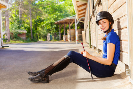 Jockey girl sitting outside a box stall with whip Stock Photo