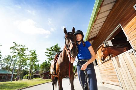 Ragazza felice della puleggia tenditrice che abbraccia il suo cavallo di baia di razza Archivio Fotografico - 86945894