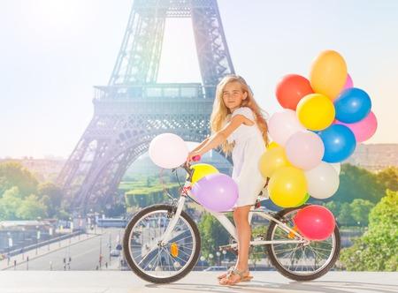 Beautiful girl cycling through Paris with balloons