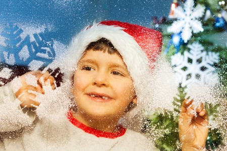 Boy behind decorated for Christmas window