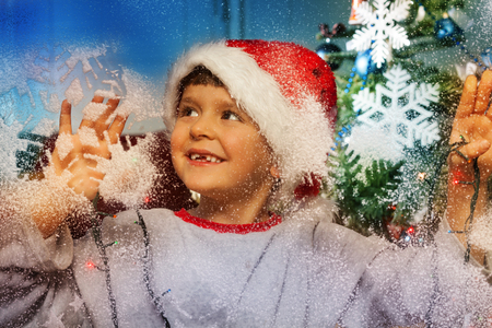Boy behind decorate window before Christmas Stock Photo