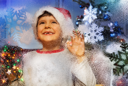 Little boy behind window with snowflake smiling Stock Photo