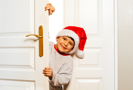 Boy looking out from the white door in Santa hat