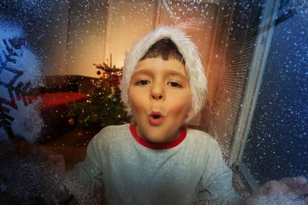 Little boy blowing on frosty window with snowflake