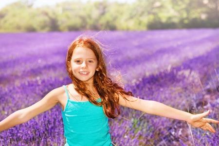 Happy red-headed girl having fun in lavender field