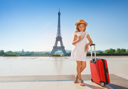 Little traveler with suitcase reading map in Paris Stock Photo