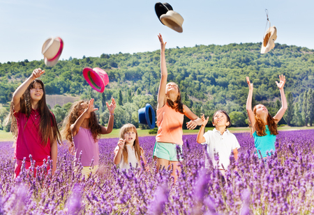 playmates: Niños alegres lanzando sombreros en el campo de lavanda