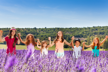 Happy children standing together in lavender field