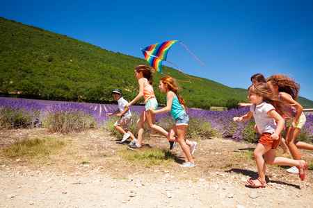 Happy children flying colorful kite in summer