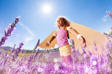 Girl pretending to be a bird in lavender meadow