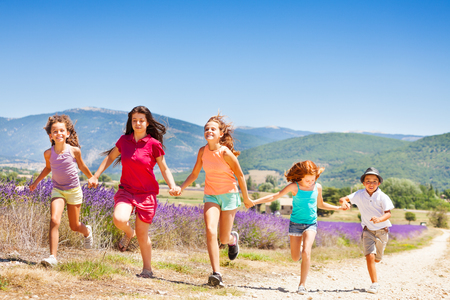 Happy kids running together through lavender field